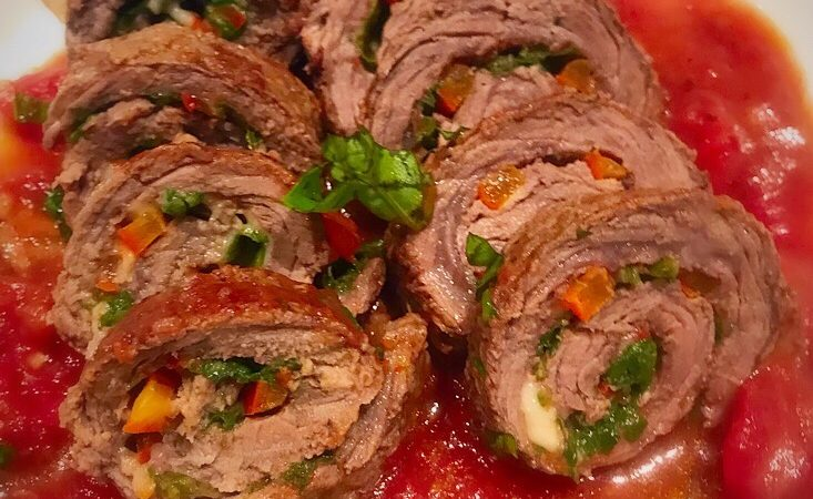 Steak rolls filled with spinach and gouda cheese in a tomato sauce